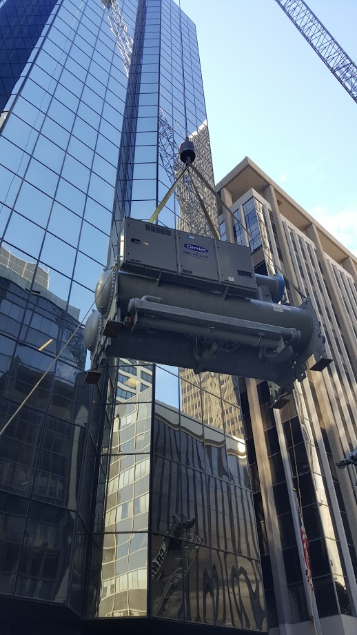 Crane lifting HVAC equipment to the roof of an office tower