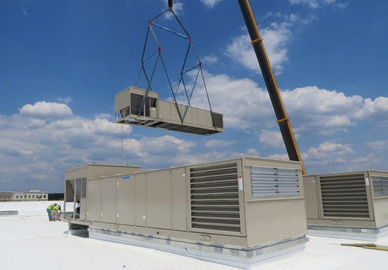 HVAC equipment being installed by a crane on a rooftop in southern California.