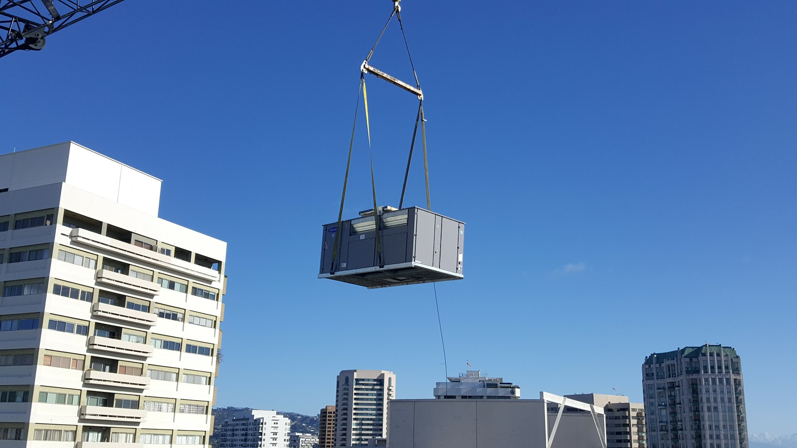 Carrier HVAC unit being lifted by a crane