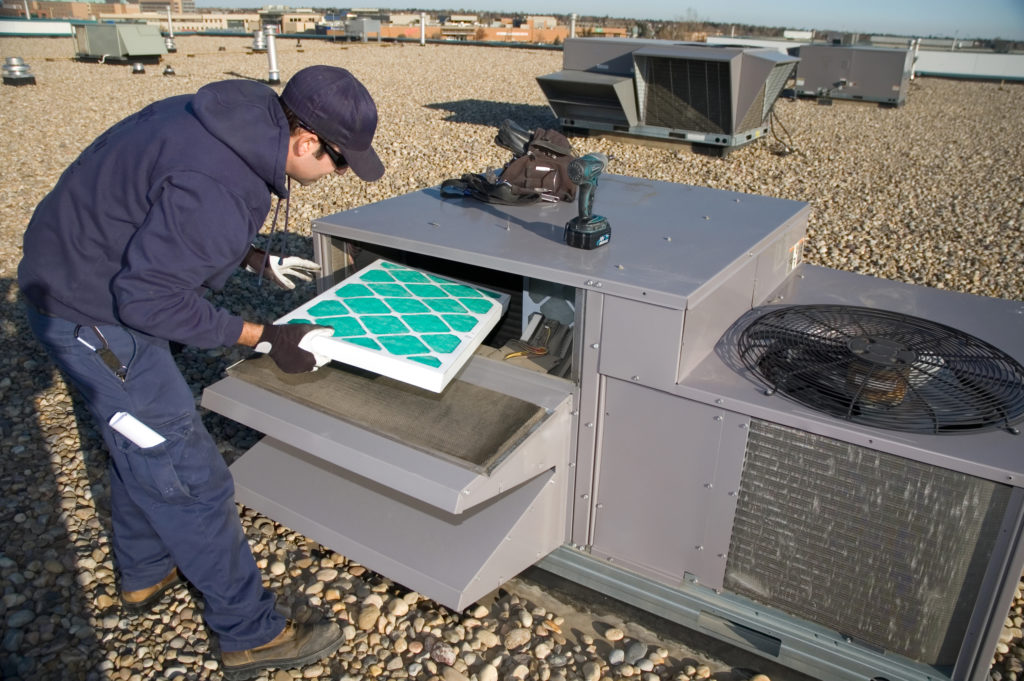 HVAC technician changing an air filter in a rooftop unit